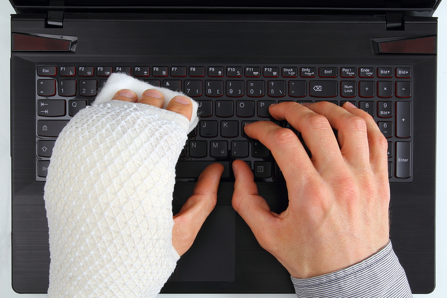 Working on a notebook with hand injury - Los Angeles personal injury lawyer