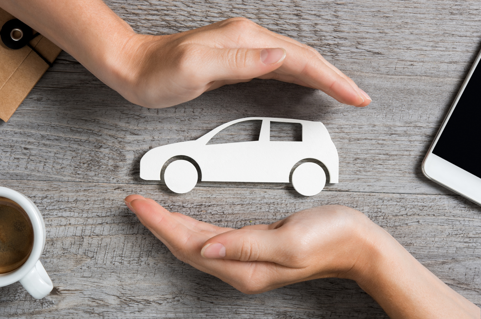 hands-holding-car-paper-cut-out