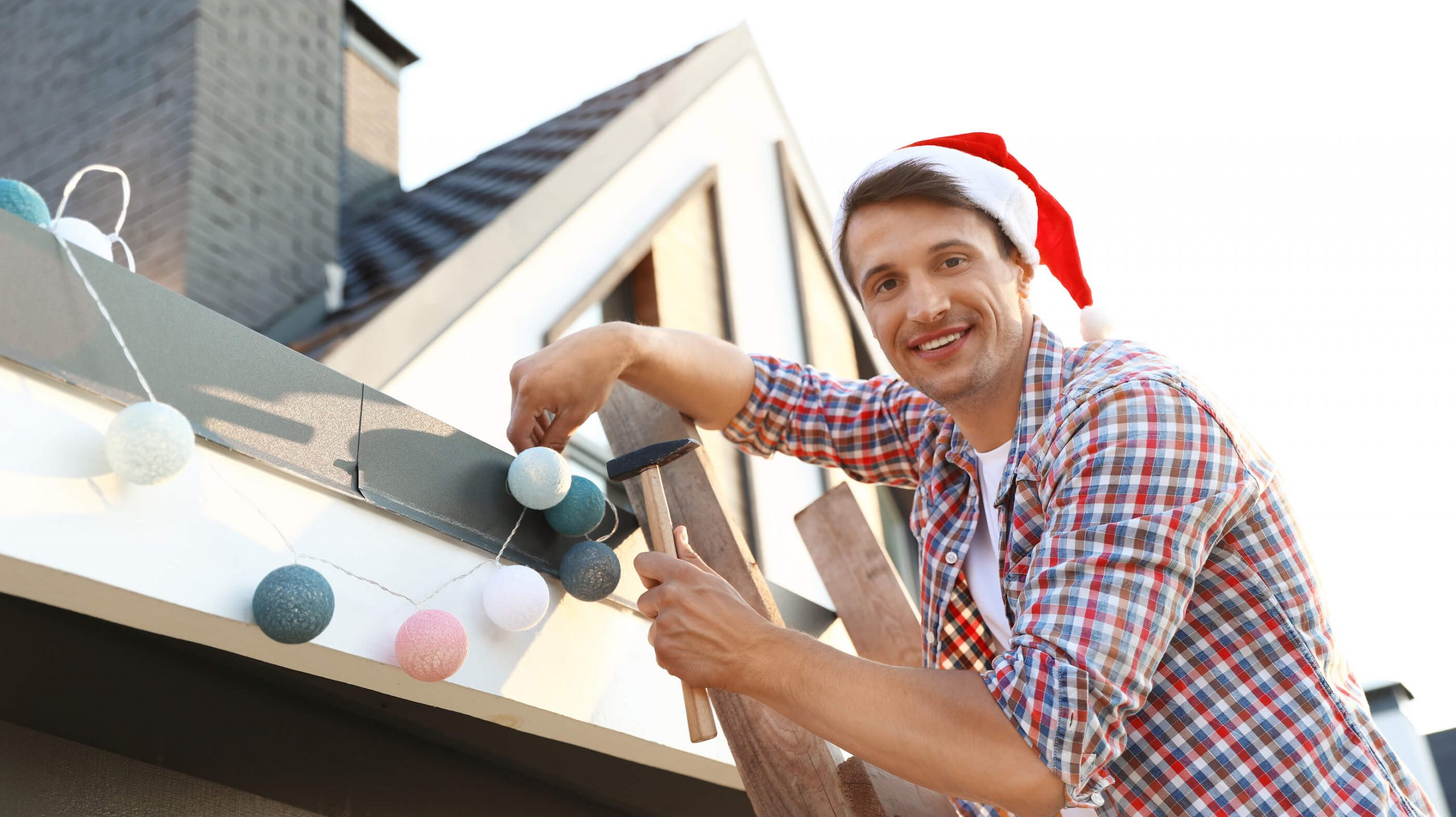 Man-In-Santa-Hat-Decorating-House-with-lights-on-ladder