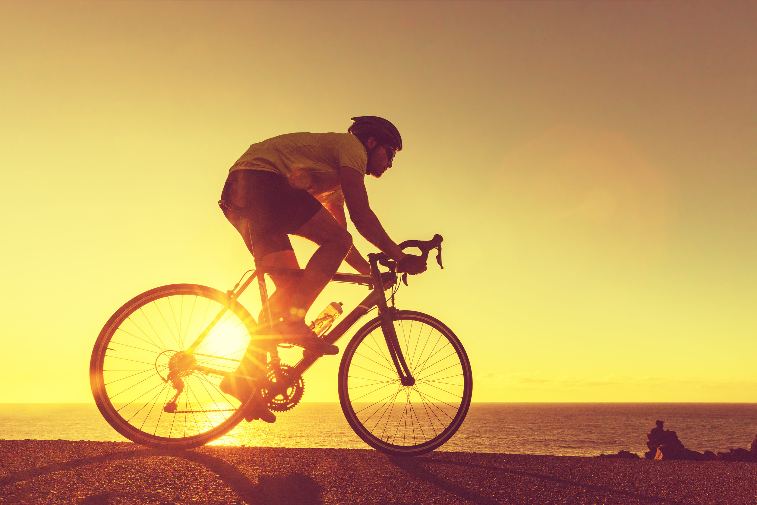 Cyclist-Riding-Bike-on-Open-Road-to-the-Sunset-Sun-Flare