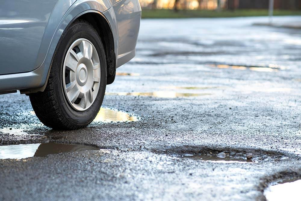 Close-Up-Of-Car-Wheel-On-A-Road-in-Very-Bad-Condition-wth-Large-Potholes-Full-of-Rain-Water