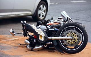 Motorbike-Accident-On-City-Street-Next-to-Parked-Car