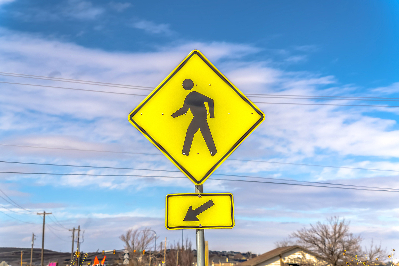 Yellow-Pedestrian-Crossing-And-Arrow-Sign-with-Cloudy-Blue-Sky-in-Background