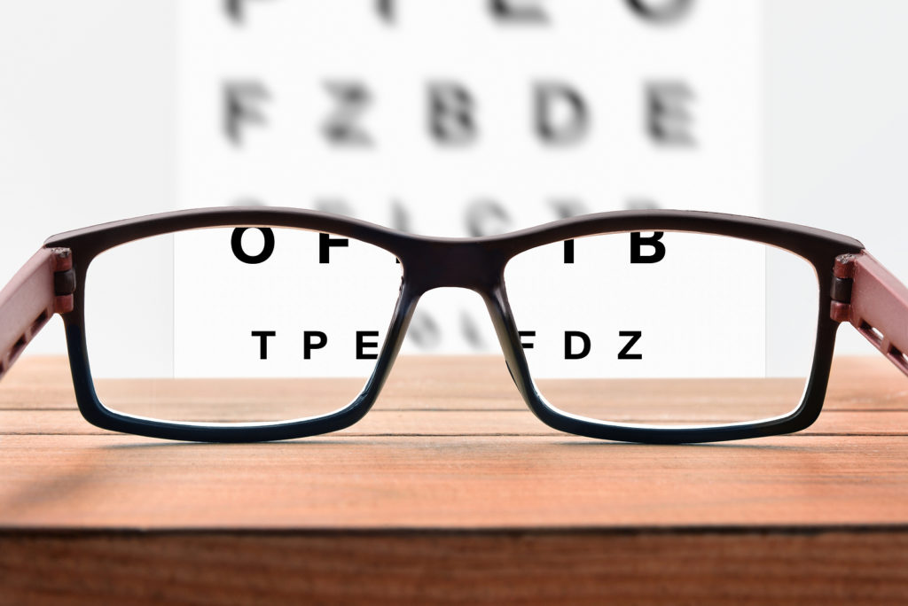 Eye-Glasses-On-Table-Looking-at-Optometrist-Alphabet-Chart