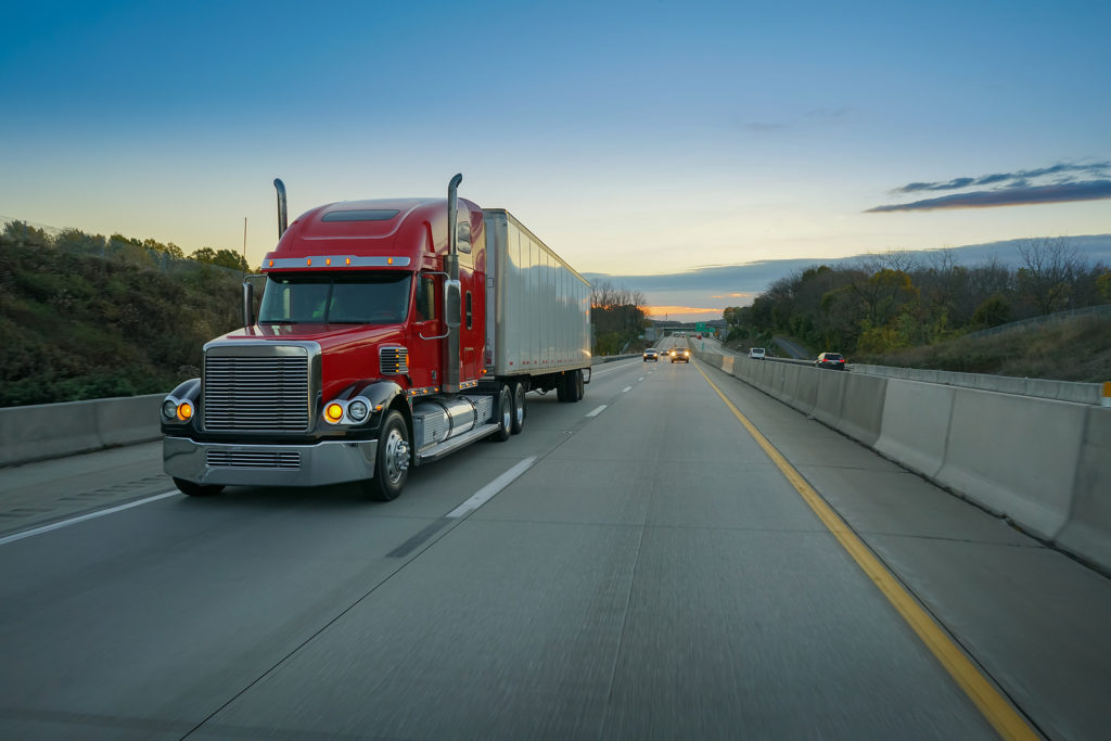 Red-Semi-Truck-Trailer-18-Wheeler-on-Highway-at-Sunrise
