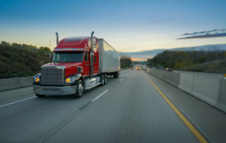 Red-Semi-Truck-Trailer-18-Wheeler-on-Highway-at-Sunrise